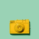 Yellow camera laying on a green background - 189309456