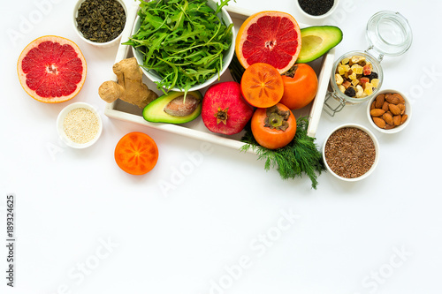 Healthy food in wooden tray: fruits, vegetables, seeds and greens on white background. Flat lay. Top view © thayra83