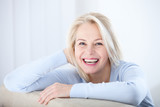 Active beautiful middle-aged woman smiling friendly and looking in camera. Woman's face closeup. Realistic images without retouching with their own imperfections. Selective focus. - 189325402
