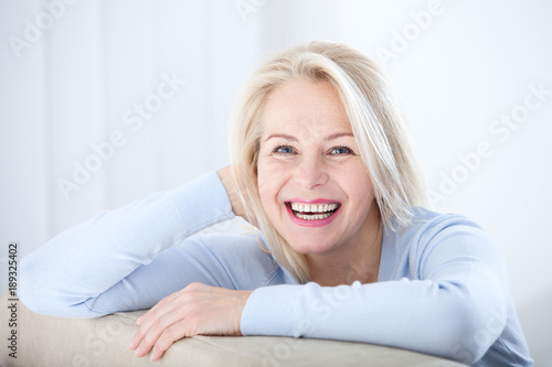 Leinwandbild Motiv Active beautiful middle-aged woman smiling friendly and looking in camera. Woman's face closeup. Realistic images without retouching with their own imperfections. Selective focus.