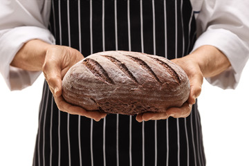 Close-up of a baker giving a loaf of bread
