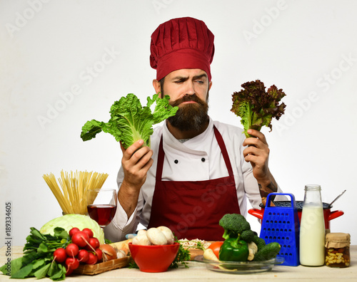 Male cook with grumpy face holding fresh lettuce. © Roman Stetsyk