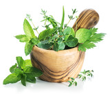 Different fresh green herbs in the wooden mortar. - 189344487