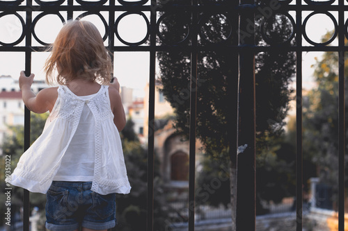 Fotobehang Athene Little girl in summer clothing playing on the fence, watching the city