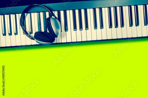 headphone on piano keys, isolated on green Poster
