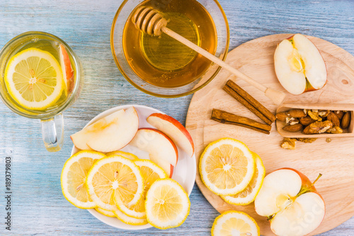 Tea with lemon, honey and apples on a rustic wooden background