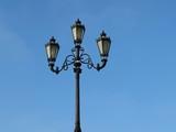 City street lantern on the background of blue sky. Vintage iron street lamp isolated - 189384009