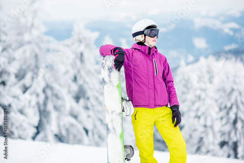 obraz lub plakat Portrait of a young woman snowboarder standing outdoors on the snowy mountains