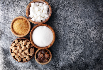 Various types of sugar, brown sugar and white on grey table