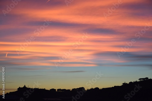 Fotobehang Koraal Tramonto con nuvole arancioni e rosa sulla collina