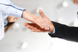Gratulacje. Powitanie nowego pracownika firmy. Dłoń kobiety i mężczyzny w  strojach biurowych podczas gestu przywitania. - 189399289