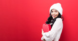 Happy young woman holding a big heart gift box on a solid background - 189427266