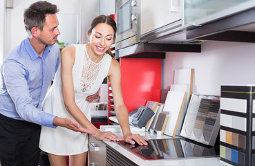 Young couple looking at kitchen tabletop in furniture workshop
