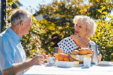 Senior woman and man having breakfast sitting in their garden outdoors in summer, eating bread rolls and drinking coffee