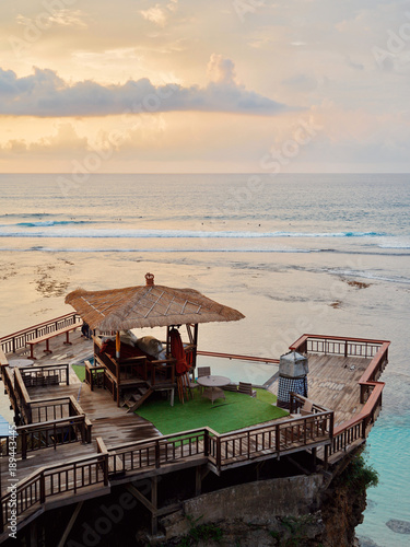 In de dag Bali A colorful sunset in Uluwatu on the island of Bali, Indonesia. View of a cafe with an infinity pool in the ocean.