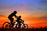 Silhouette man and bike relaxing on blurry sunrise background - 189460865