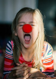 Girl with clown nose, yawning, upset, a shadow, a ray of sunshine on the face