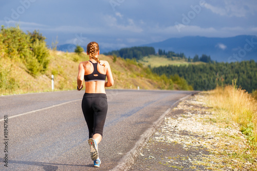 Fotobehang Hardlopen Young sporty woman jogging on mountain road. Running fitness girl in sportswear outdoor image with copy space