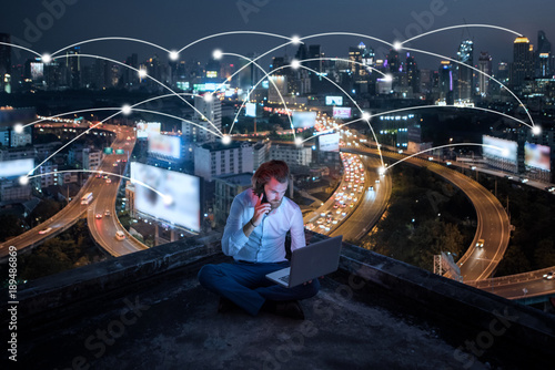 young business man sitting talking mobile phone and working at night on rooftop,business business and network technology concept