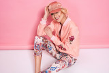 Fototapety Fashion photo of a beautiful elegant young woman in a pretty bomber, pants and a cup posing over pink background. Fashion photo