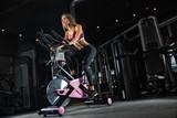 Fototapety Beautiful girl in sportswear doing exercises in a beautiful gym cardio training