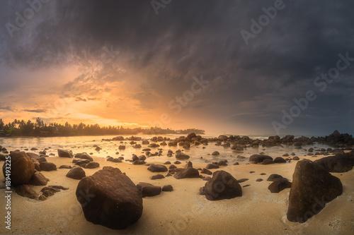 Tropical beach with rocks on sand coast of ocean