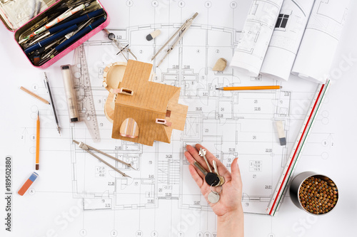 Architect holding keys at house model in office