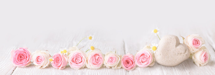 Pink roses and stone heart on rustic wooden background  © Floydine