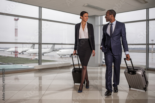 Joint business trip. Full length portrait of cheerful confident elegant colleagues are going along airport with luggage. They are looking at each other with joy. Copy space and airplanes in background