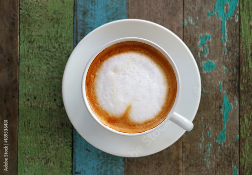 Papiers peints Cafe Hot Coffee with Heart Shaped Latte Art in a White Cup on Colored Rustic Style Wooden Table,Top View with Selective Focus