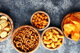 Salty snacks. Pretzels, chips, crackers in wooden bowls. - 189546432