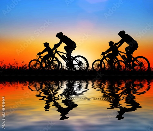 Silhouette man and bike relaxing and water reflection on blurry sunrise background