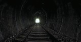 View from inside of old dark long railroad tunnel with bright light in the end - 189563044
