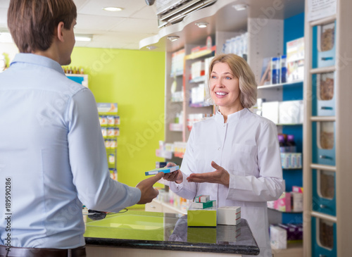 In de dag Apotheek Ordinary guy talking to pharmacist at pharmacy