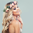 Beautiful Girl with Cute Smile, Makeup and Flowers. Young Woman with Blonde Curly Hair Smiling