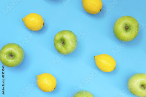 Top view of colorful fruit pattern of fresh lemon and apple on blue background - 189595011