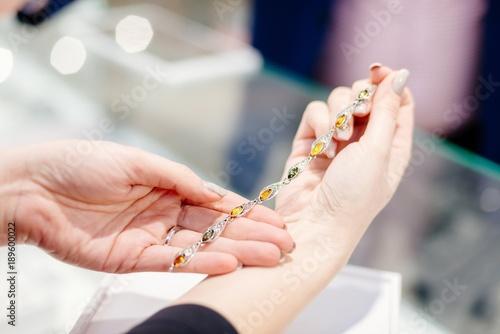 Właścicielka sklepu jubilerskiego prezentująca srebrną bransoletkę z bursztynem.