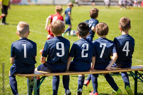 Kids sport team sitting on a bench. Group of kids soccer players. Children football club. Football soccer tournament game for children. Boys kicking soccer on grass pitch. Children play sport outdoors