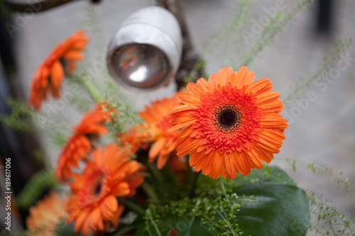 Fotobehang Fiets flowered retro bicycle decorated with orange flowers, gerberas