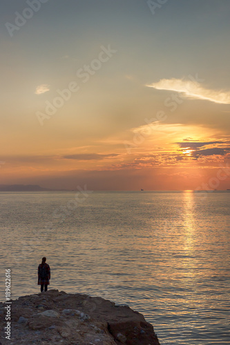 Foto op Canvas Zee zonsondergang Silhouette of woman and sea sunset. Athens, Greece