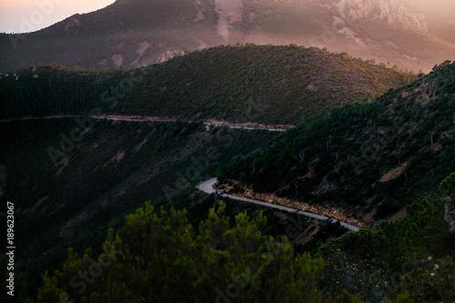 Fotobehang Zwart kleine kurvige Strasse am Berghang durch Wald