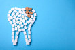 Sugar destroys the tooth enamel and leads to tooth decay. Sugar cubes are laid out in the form of a tooth and brown sugar symbolizes caries. Copy space for text