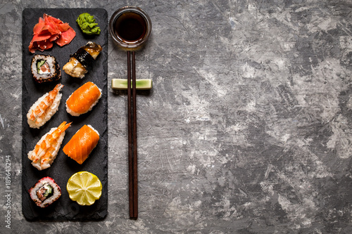 Keuken foto achterwand Sushi bar sushi and sushi rolls, sushi nigiri on stone plate on dark background, mustard wasabi, and ginger