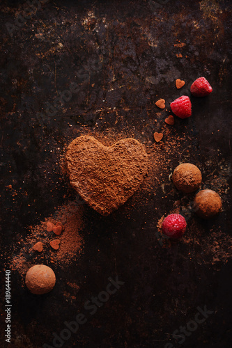 Truffles in heart shape, for valentine's day on old black metal background.