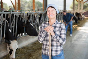Female farmer posing on background of cows in stall