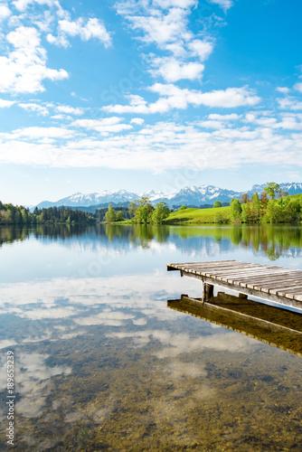 idylliczny-jezioro-z-drewnianym-molem-przy-stopa-alps-portret