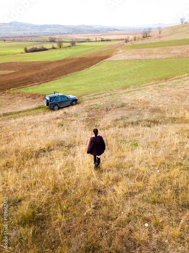 Staande foto Beige A girl going towards a car in a field . drone portait shot of a girl in a field