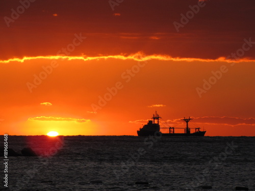Fotobehang Baksteen Cargo ship on the Adritic sea in sunset. Europe. Adriatic sea of Mediterranean area. Montenegro`s coastline. Atumn 2012.