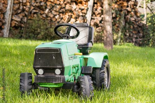 Fotobehang Trekker Spielzeug Traktor auf Wiese