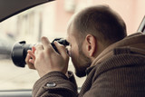 Investigator or private detective or reporter or paparazzi sitting in car and taking photo with professional camera - 189672482